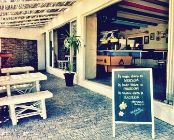 Boardhouse is a vibrant beach bar and kite shop with artistic décor and deep house beats on the doorstep of the gorgeous, sweeping Blouberg beach. With postcard views of Table Mountain, Boardhouse is an absolute favourite of locals in the area and offers a selection of beverages. The staff have awesome personalities while the proprietor, Su Le Roux, is the heart and soul of the place. A home away from home where the kegs don't run dry and the people become more than friends - family for life.